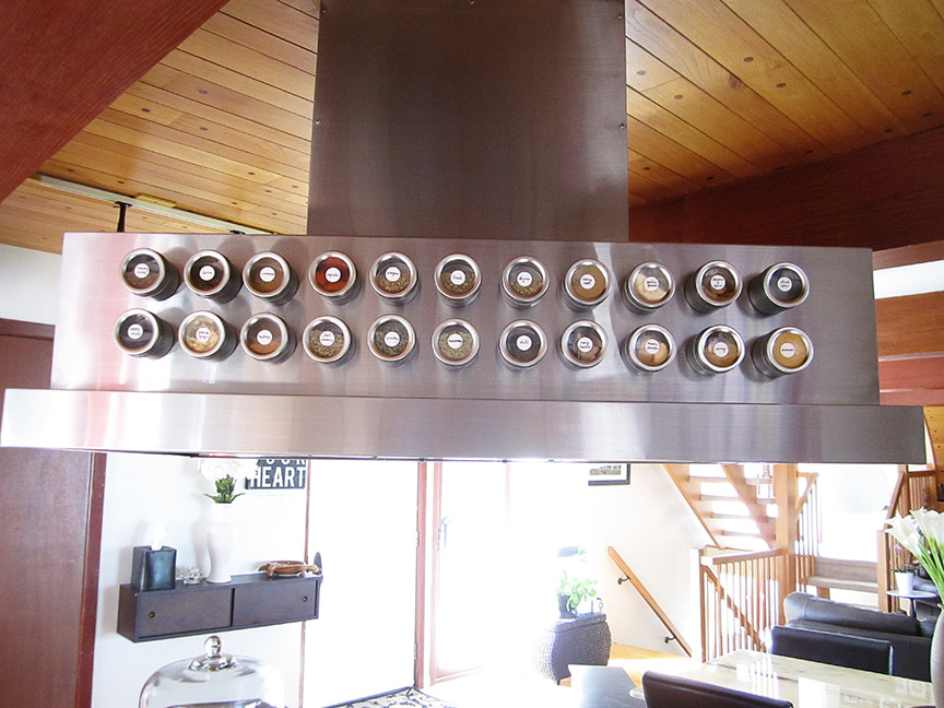 Organize your spices in magnetic tins & stick 'em right on the range hood for easy access.